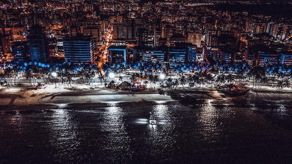 Orla de Maceió à noite com barco no mar da Ponta Verde